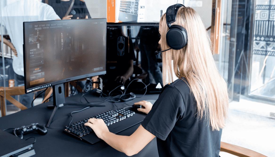 On voit une femme informaticienne travailler devant son ordinateur et son clavier.
