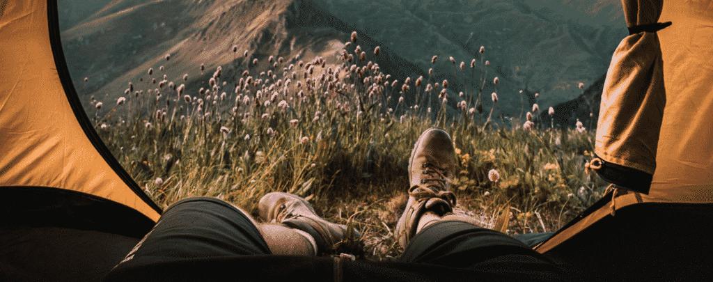 Un digital nomad campe en montagne et travaille à distance.