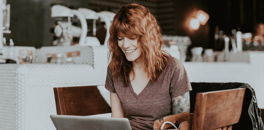 Une femme écrit un nouvel article sur le blog qu'elle a créé.
