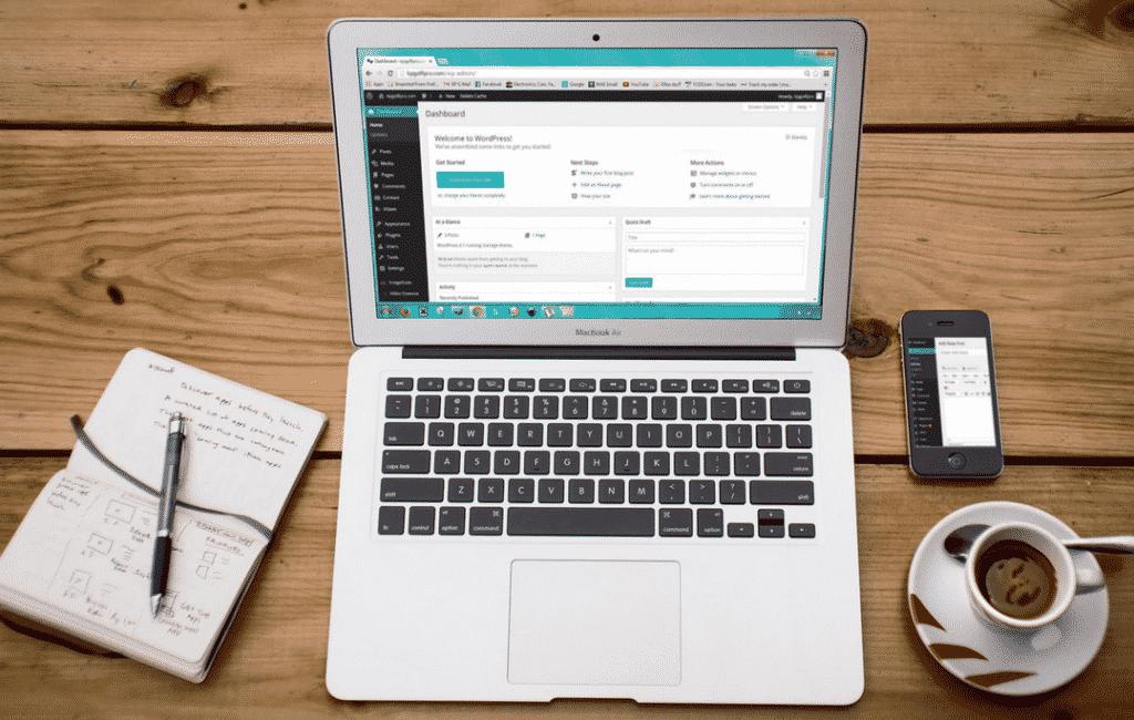 Voici le bureau d'un blogueur : carnet de notes, ordinateur, smartphone et café