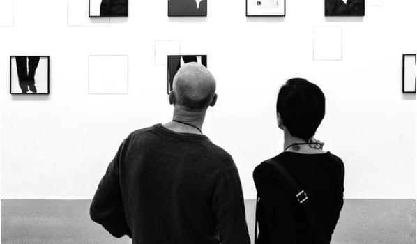 Un dropshipper en train de vendre des oeuvres d'art dans une gallerie, il fait du dropshipping hight ticket en noir et blanc.